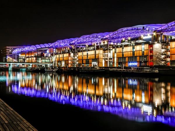 The shopping centre Confluence has a luminouus facade at night.