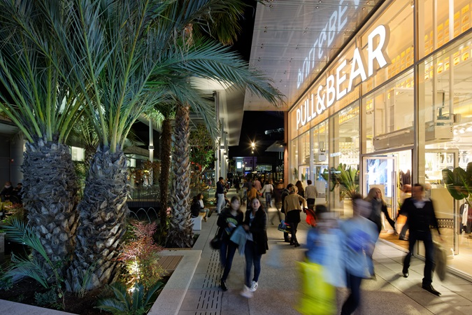 Customers stroll at nightfall in Polygone Riveria, past the store Pull&Bear