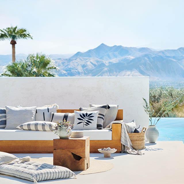 En solig uteplats med soffa och kuddar