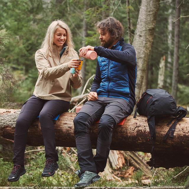 En kvinna och en man sitter på en trädstam i skogen. Mannen häller upp kaffe till kvinnan från en termos.