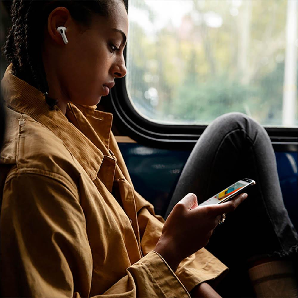En kvinna med airpods i öronen tittar på sin mobil