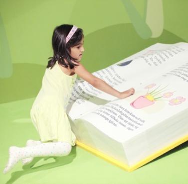 Flicka läser en stor bok